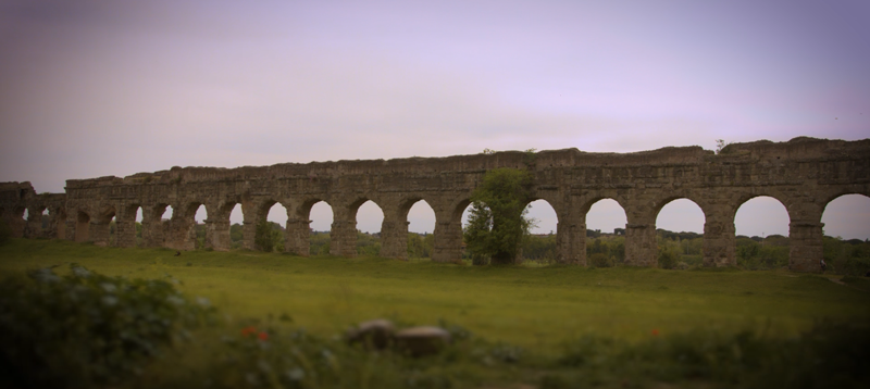 View along a section of a stone aqueduct in a field