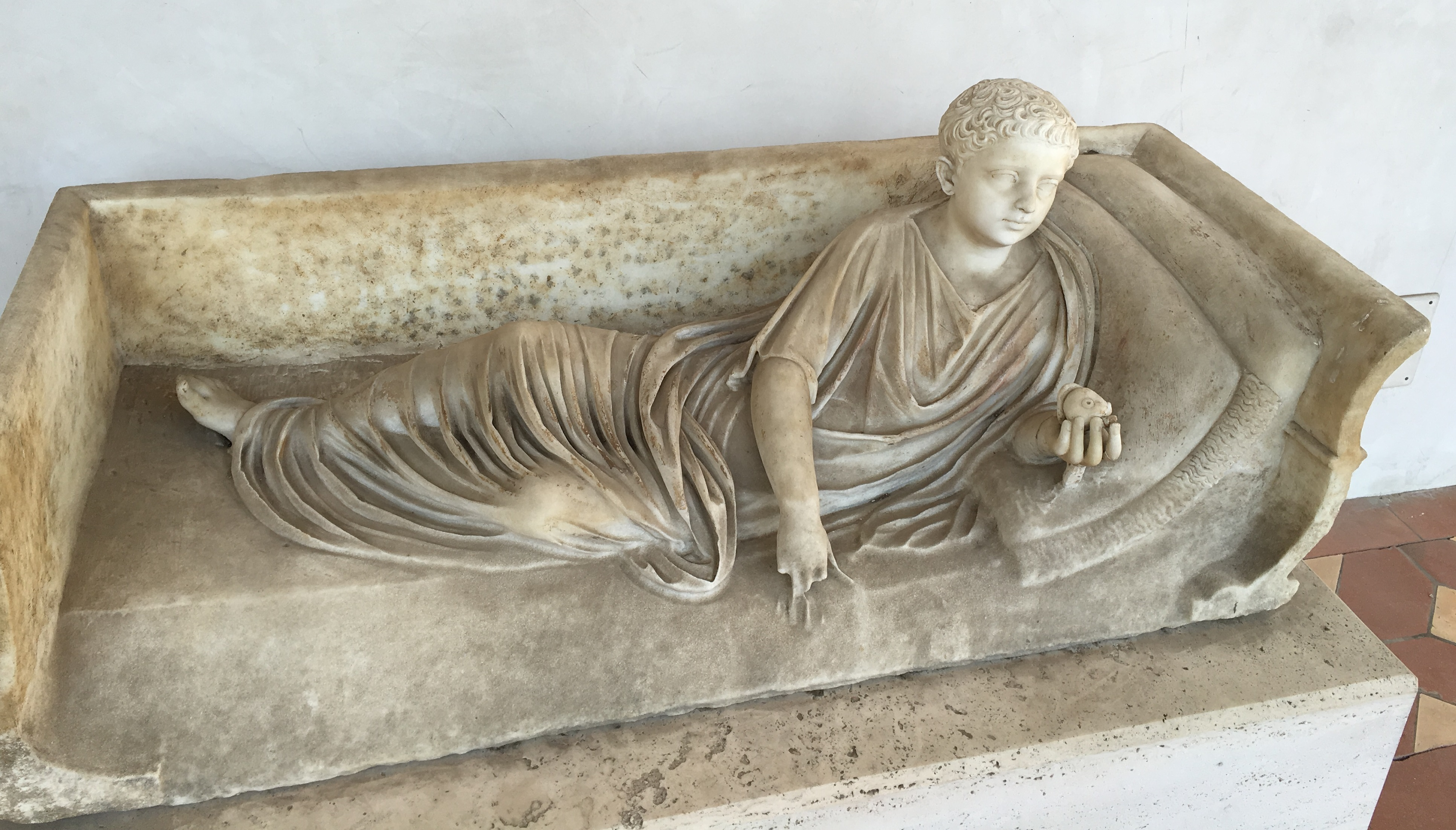 Marble statue on the lid of a sarcophagus