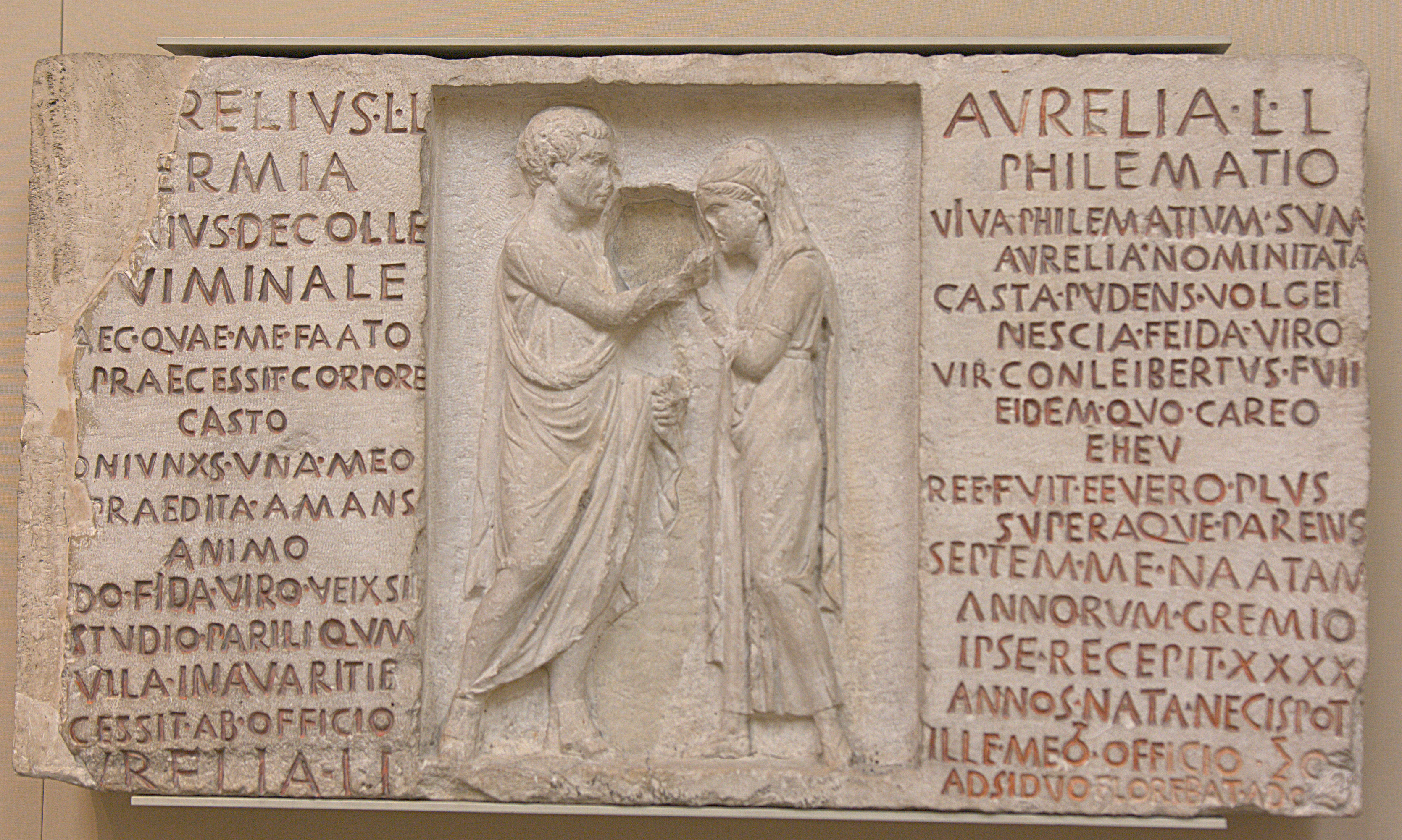 Marble tombstone with relief of two figures in the centre, with an inscription either side