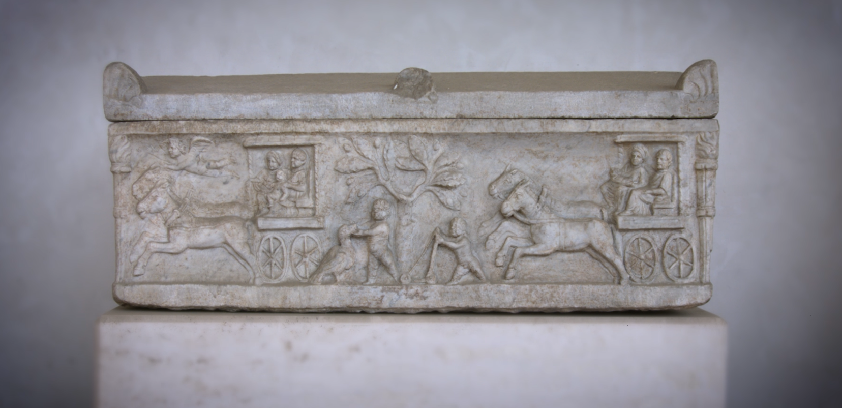 Small marble sarcophagus, with a relief depicting two horse drawn carts, a boy playing with a bird and an child with a walker.