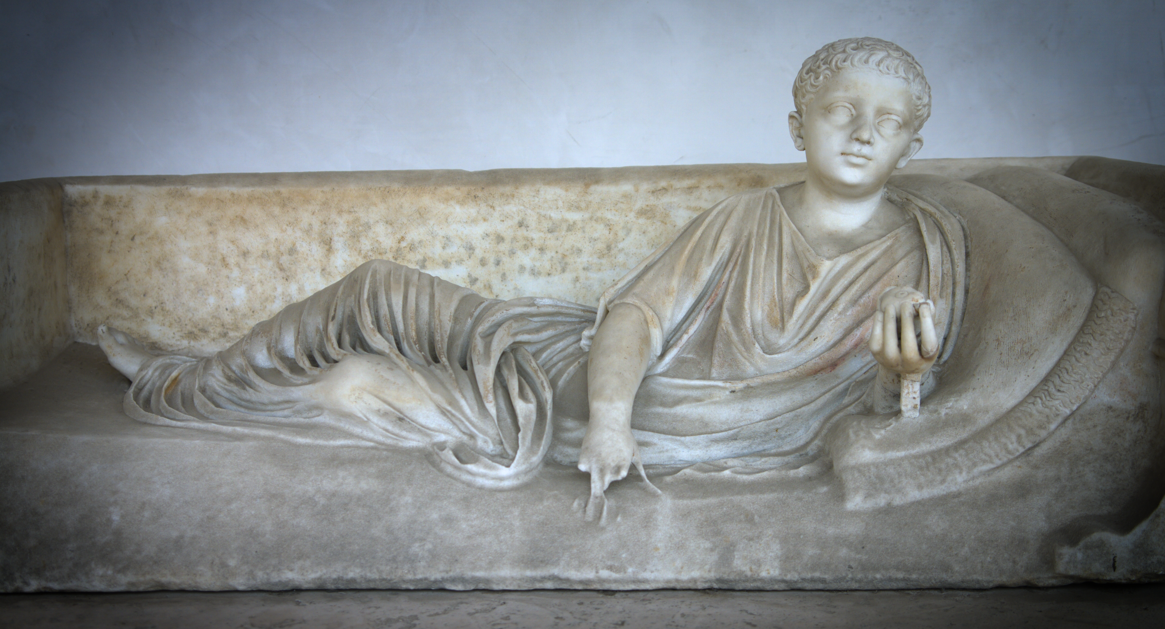 Marble statue of a young man in a toga holding a fruit